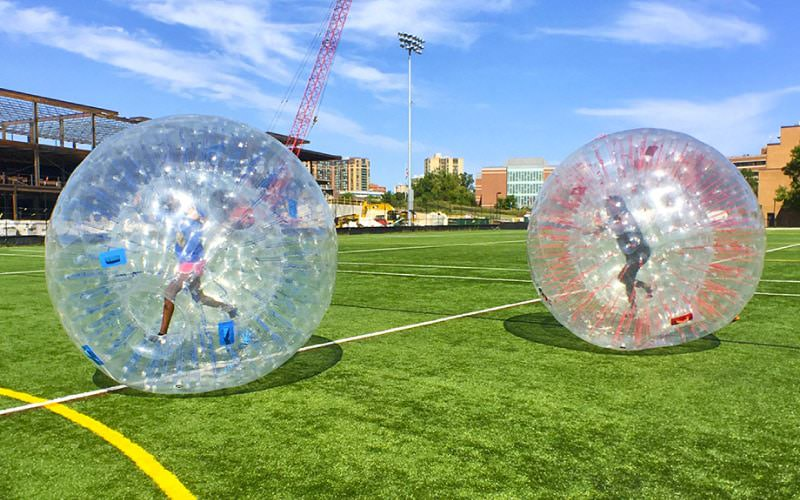 Two girls running inside Hamster Balls on a turf field in Maryland