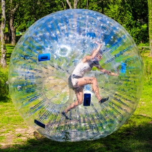 One Girl inside a Hamster Ball running around an outdoor field in Baltimore, Maryland